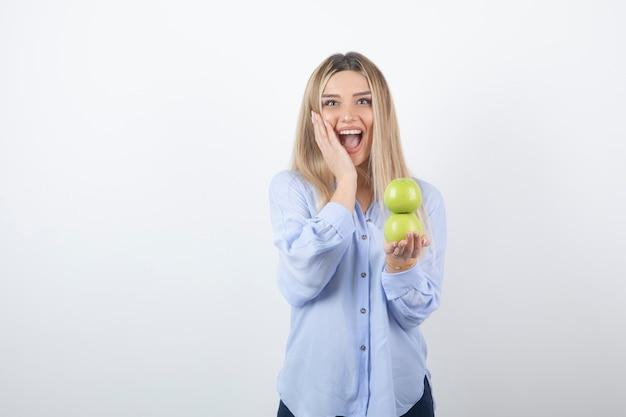 Portrait d'un modèle de jolie fille debout et tenant des pommes fraîches.