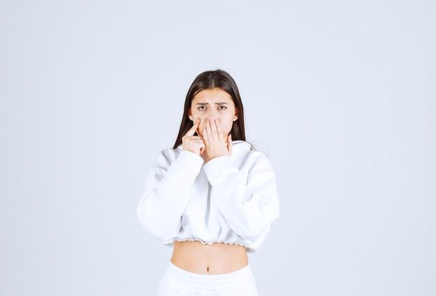 Portrait d'un modèle de jolie jeune fille couvrant la bouche avec une main.