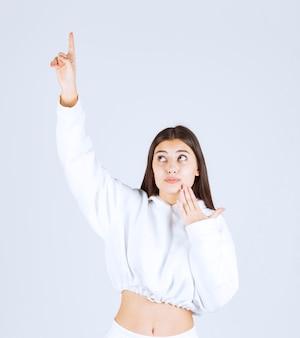 Portrait d'un modèle de jolie jeune fille pointant vers le haut.