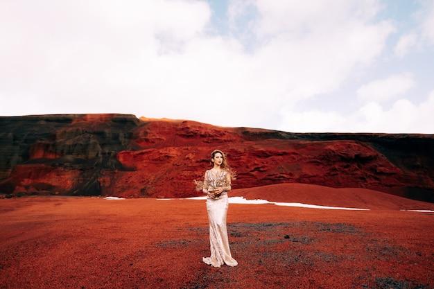 Portrait D'un Modèle De Mariée Dans Une Robe De Soirée De Mariage D'or Dans Une Carrière De Sable Jaune-rouge Dans Le Photo Premium