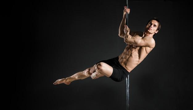 Portrait de modèle masculin effectuant une pole dance