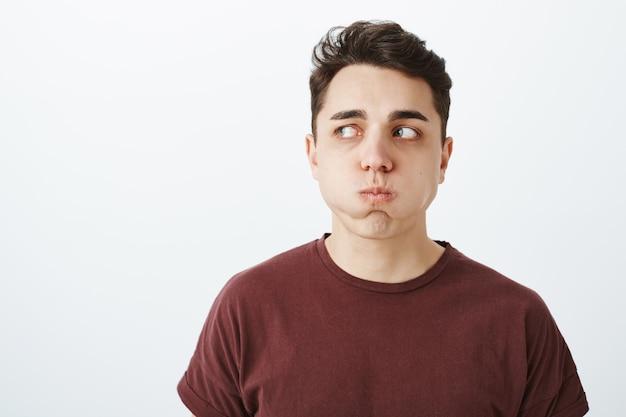 Portrait de modèle masculin européen drôle en t-shirt rouge