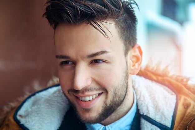 Portrait de modèle masculin mignon au look décontracté. regardant ailleurs et souriant.