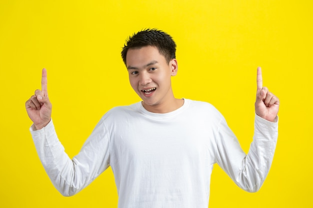Portrait de modèle masculin pointant le doigt vers le haut et souriant sur le mur jaune