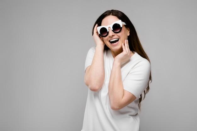 Portrait de modèle de taille plus belle émotionnelle en lunettes de soleil debout