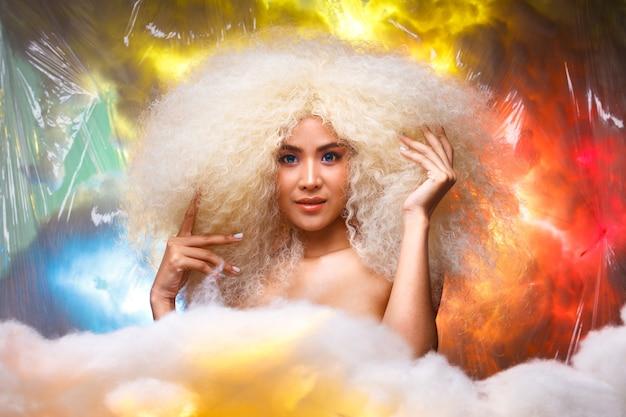Portrait de la moitié du corps des années 20 asiatiques caucasiennes belle femme blonde cheveux afro maquillage haute couture. jolie fille souriante regarde la caméra sur un nuage de ciel coloré rouge bleu jaune pastel en studio