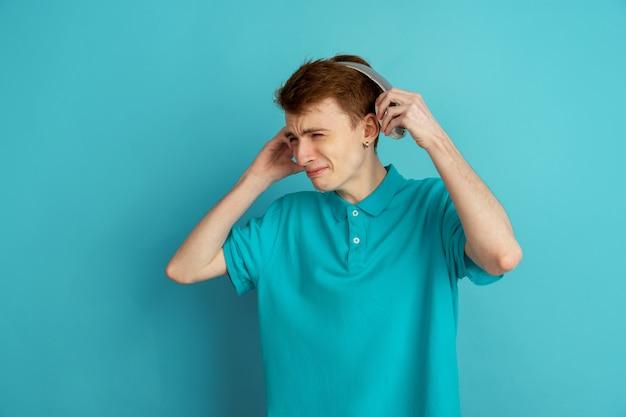 Portrait monochrome de jeune homme sur fond bleu