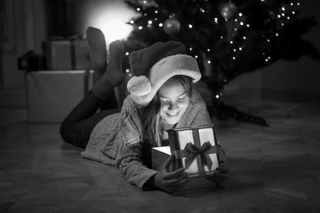 Portrait monochrome d'une petite fille heureuse allongée avec une boîte-cadeau sous l'arbre de noël