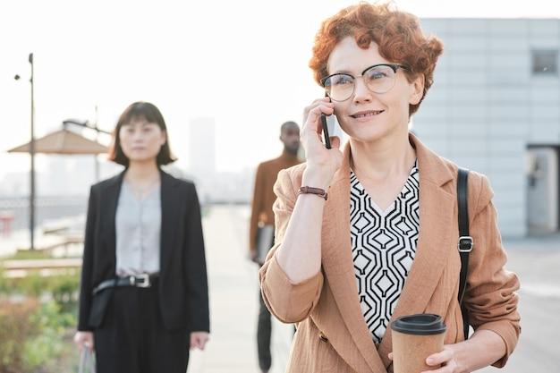 Portrait moyen horizontal d'une belle femme mature aux cheveux roux bouclés parlant au téléphone avec quelqu'un sur le chemin du retour après avoir terminé sa journée de travail