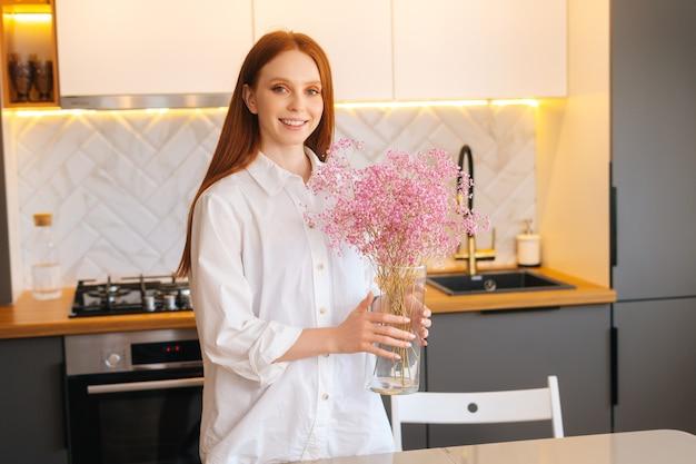 Portrait moyen d'une jolie jeune femme créative souriante décorant la maison avec de la gypsophile séchée