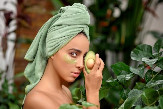 Portrait d'une mystérieuse brune avec une serviette sur la tête et des patchs de gel sous les yeux