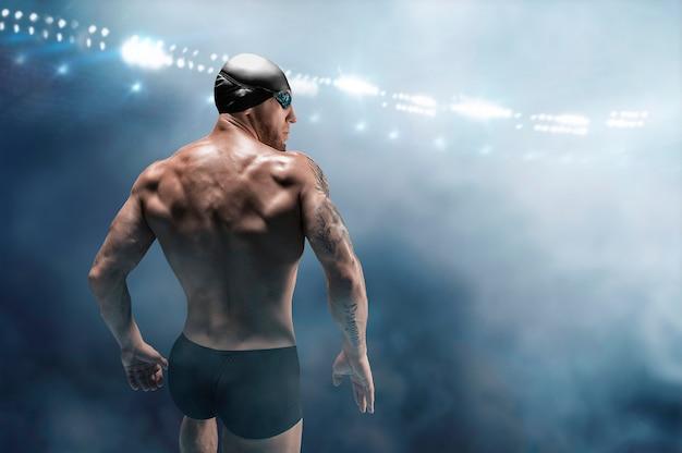 Portrait d'un nageur sur le fond d'une arène sportive. vue arrière.
