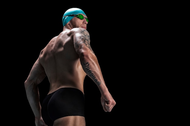 Portrait d'un nageur sur un mur noir. vue arrière.