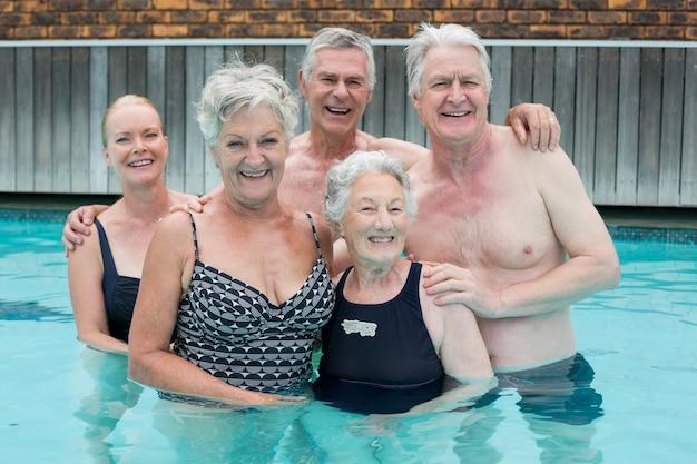 Portrait de nageurs seniors debout dans la piscine