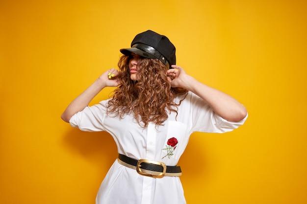 Un portrait naturel d'une femme aux cheveux bouclés dans une casquette noire et une chemise blanche. la femme tient sa casquette et regarde ailleurs.