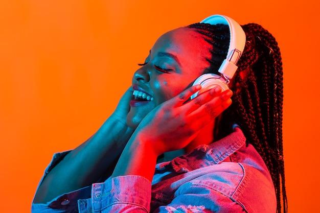 Portrait de néon de jeune femme noire écouter de la musique dans les écouteurs.