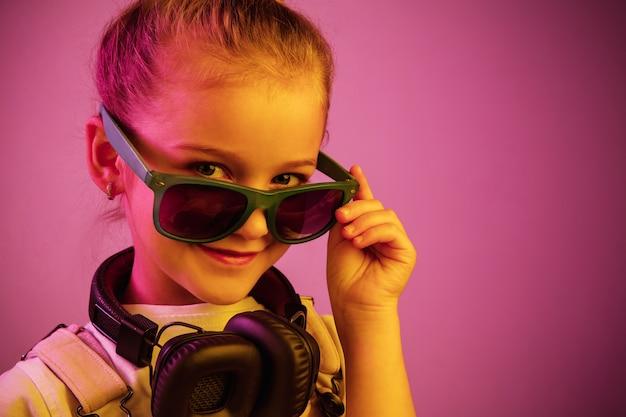 Portrait de néon de jeune fille avec des écouteurs appréciant la musique.