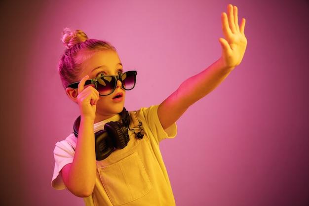 Portrait de néon de jeune fille effrayée avec des écouteurs appréciant la musique. mode de vie des jeunes, émotions humaines, enfance, concept de bonheur.
