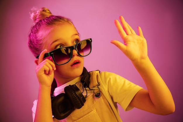 Portrait de néon de jeune fille effrayée avec des écouteurs appréciant la musique.