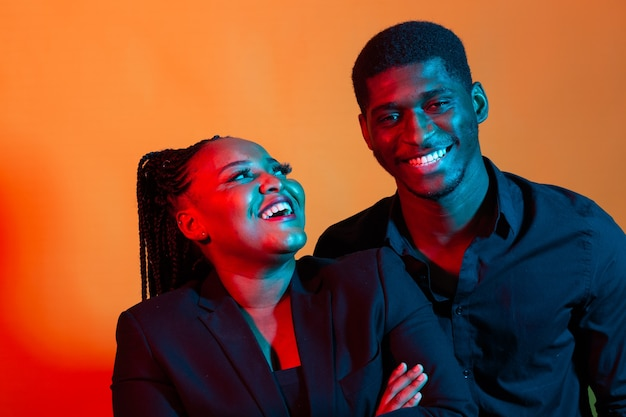 Portrait de néon sombre de jeune homme afro-américain et femme. lumière rouge et bleue.