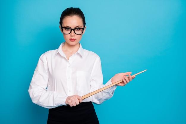 Portrait de nice coacher attrayant tenant dans les mains l'école secondaire de bâton en bois isolé sur fond de couleur bleu vif