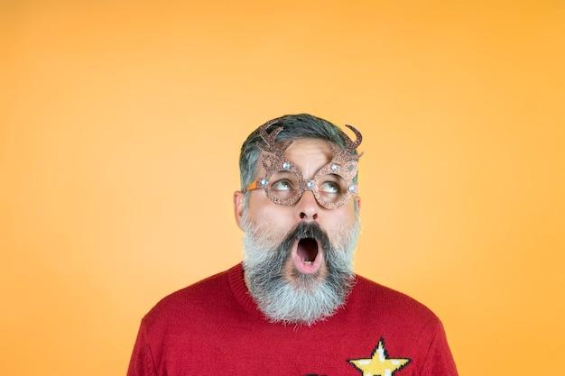 Portrait de noël de l'homme hipster surpris regardant des cornes de cerf de lunettes