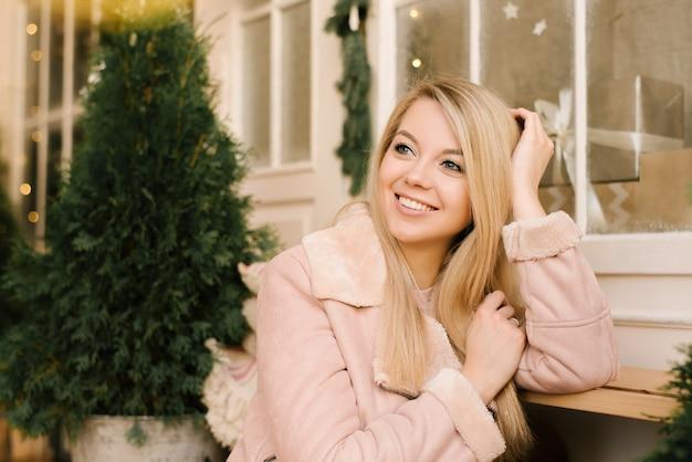 Portrait de noël d'une jeune fille en robe rose et manteau en peau de mouton avec le décor de noël de la maison dans un intérieur élégant. une femme se prépare à célébrer noël et le nouvel an