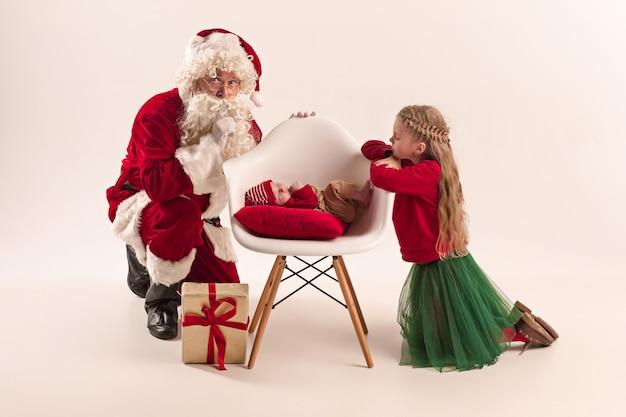 Portrait de noël de mignonne petite fille nouveau-né, jolie soeur adolescente, vêtue de vêtements de noël et père noël avec boîte-cadeau