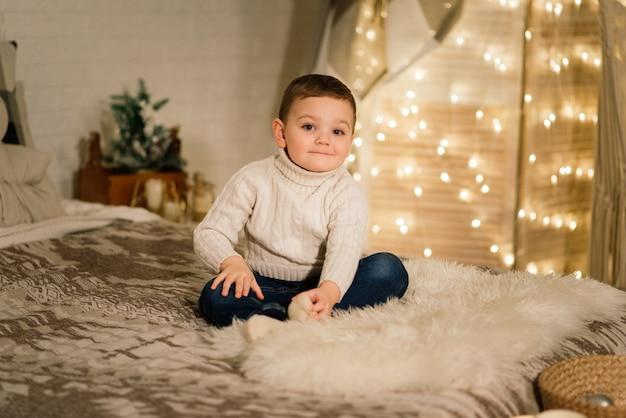 Portrait de noël d'un petit garçon mignon, vêtu de vêtements de noël, tourné en studio, heure d'hiver