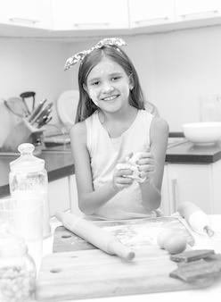 Portrait noir et blanc de fille préparant la pâte sur la planche en bois