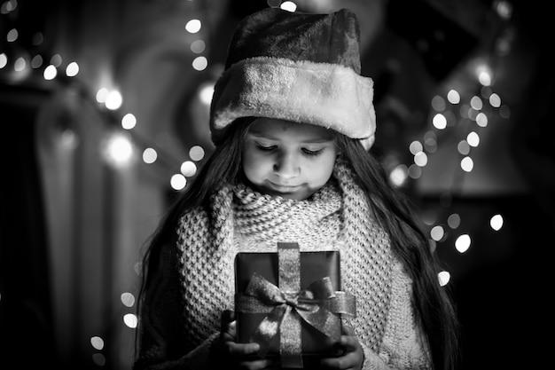 Portrait noir et blanc d'une fille souriante ouvrant la boîte de cadeau de noël