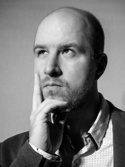 Portrait noir et blanc d'un homme d'âge moyen vêtu d'une veste et d'une chemise, qui regarde pensivement sur le côté, en appuyant un doigt sur sa joue, sa barbe, un peu de cheveux sur la tête, de race blanche