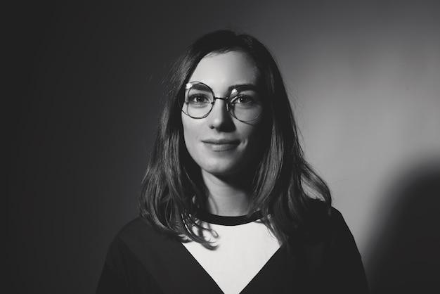 Portrait noir et blanc de jeune femme hipster portant des lunettes rondes