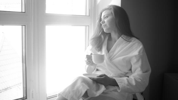 Portrait noir et blanc d'une jeune femme en peignoir assise à une grande fenêtre et buvant du café