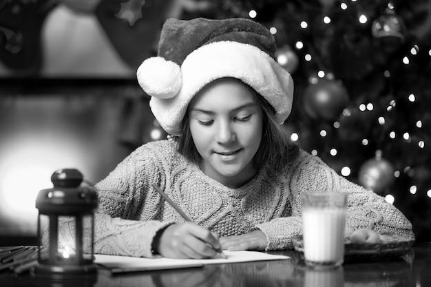 Portrait noir et blanc d'une jolie fille écrivant une lettre au père noël au salon
