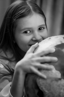 Portrait noir et blanc d'une jolie fille posant avec un globe terrestre