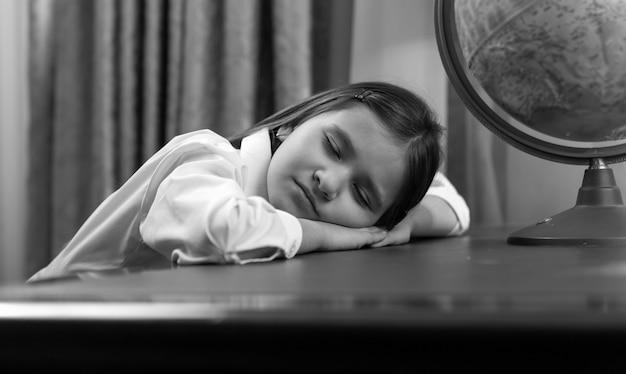 Portrait noir et blanc d'une jolie fille s'endormant en faisant ses devoirs