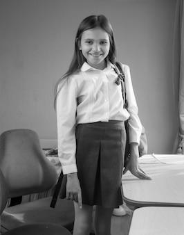 Portrait noir et blanc d'une jolie fille avec un sac d'école debout derrière un bureau dans la chambre