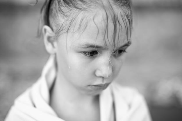 Portrait noir et blanc de la petite fille aux cheveux mouillés et une serviette chaude sur la plage