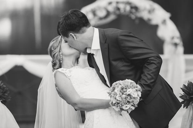Portrait noir et blanc tonique du marié et de la mariée s'embrassant au parc contre l'arche florale