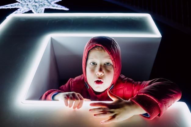 Portrait de nuit drôle de garçon avec des grimaces éclairées par des néons.