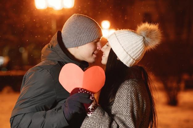 Portrait de nuit en plein air de jeune couple avec coeur de papier dans la rue