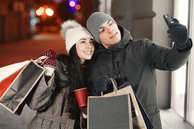 Portrait de nuit en plein air de jeune couple avec des sacs à provisions