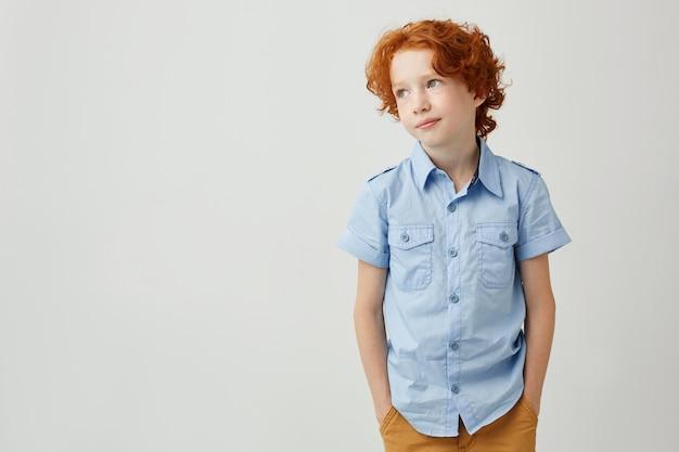 Portrait o petit garçon au gingembre avec des taches de rousseur se tenant la main dans les poches, souriant doucement et regardant de côté
