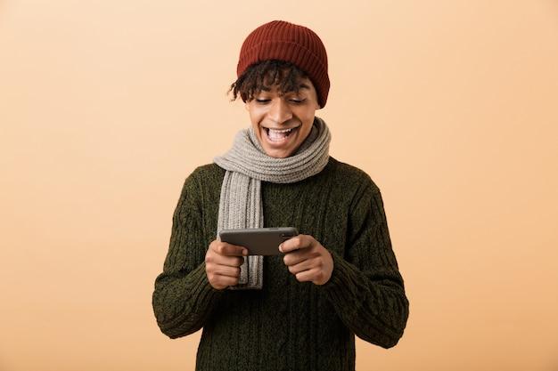 Portrait of african american gamer boy wearing hat et écharpe à jouer à des jeux vidéo sur smartphone, isolé sur mur jaune