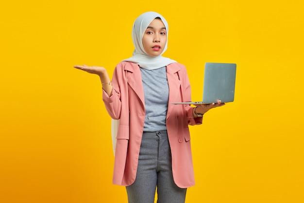 Portrait of asian woman holding laptop et confus isolé sur fond jaune