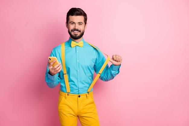 Portrait of attractive guy confiant holding cell puling jarretelles