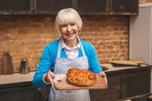 Portrait of attractive smiling happy senior age woman is cooking on kitchen. grand-mère faisant une pâtisserie savoureuse.
