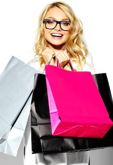Portrait of beautiful cute happy sweet smiling blonde woman woman holding in her hands big shopping sacs colorés dans des vêtements hipster isolated on white