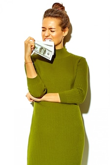 Portrait of beautiful happy cute smiling brunette woman girl in casual green hipster summer clothing isolated on white holding dollar banknote in mouth